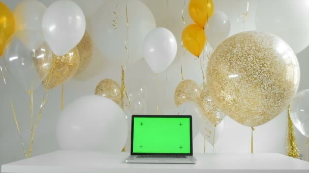laptop with isolated green screengolden and silver balloons background new year concept