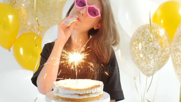Portré, fiatal, szép, szőke lány visel kúp kap gazdaság egy piros lapot születésnapi torta, és fúj a gyertyát, így a szeretnék 1080p teli