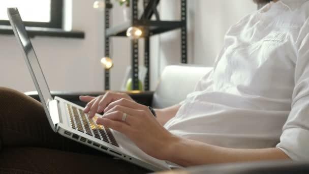 Fiatal férfi szabadúszó munka otthonról keresztül laptop, modern hordozható számítógéppel munka vintage loft, közelről a férfi kezét a 20-as 4 k számítógép billentyűzet gépelés közben csípő srác