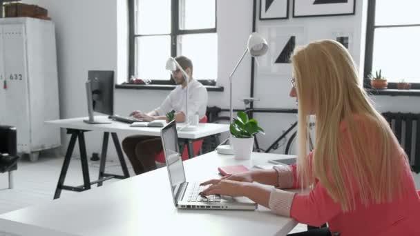 Portrét blondýna ženské obchodního partnera v její 20s sedět u svého stolu uklizené sklo před její počítač 20s 4 k