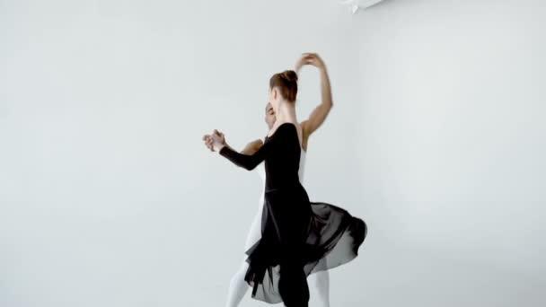 Guy in white and girl in black doing ballet in white dance studio slow motion 120fps.