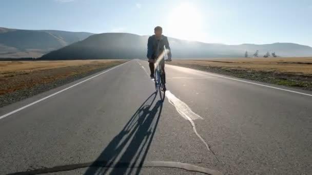 Mladý pohledný muž na koni na Retro kolo v zemi silnici. Sportovní chlap, jízda na kole na trati. Mužské cyklistu jedoucího pevné ozubené kolo na silnice. Zdravý aktivní životní styl 20s 4 k