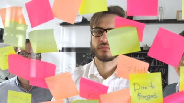 Muž post v rychlé poznámky během setkání v kanceláři na štítku je napsáno Idea
