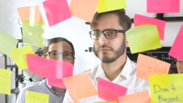Muž post v rychlé poznámky během setkání v kanceláři na štítku je napsáno tým