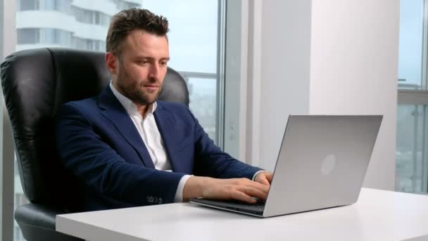 Podnikatel v oblasti formálního oblečení, pomocí přenosného počítače v kanceláři