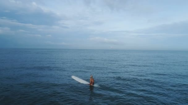 Aerial view: girl relaxing sitting at surfboard slow motion
