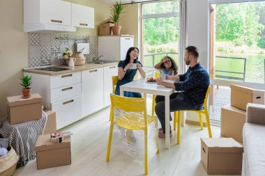 Happy mixed race family Family Group Move in Rent Real Estate. Positive Looking at Relocating or Unpacking of Carton Pack by Playful Dad