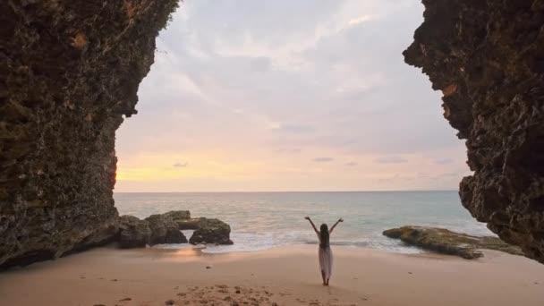 Dívka tekoucí v mělké vodě při západu slunce. Dívka v bílých šatech běží na okraji vody u moře. Jsem spokojený s mořem a pláží. Zkušenosti se svobodou