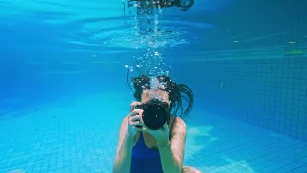 junge Frau taucht ins Wasser. Blick unter Wasser, Gischt. Sommerferienkonzept, Sprung ins Becken, Mädchen schwimmen mit Kamera unter Wasser.