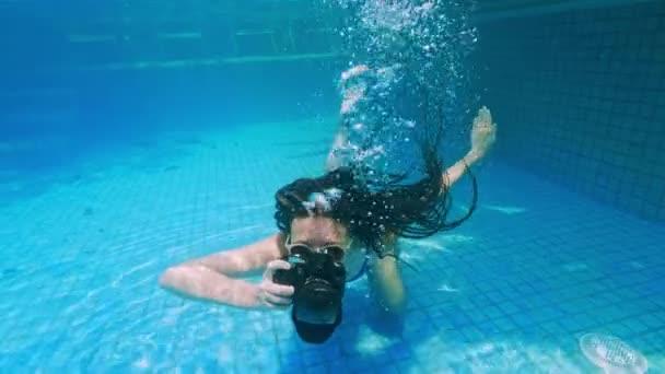 reisendes Mädchen in Asien. glückliche junge Frau mit schönen langen Haaren schwimmen unter Wasser mit Kamera in Pool von heißen Quellen. Indonesien, bali.