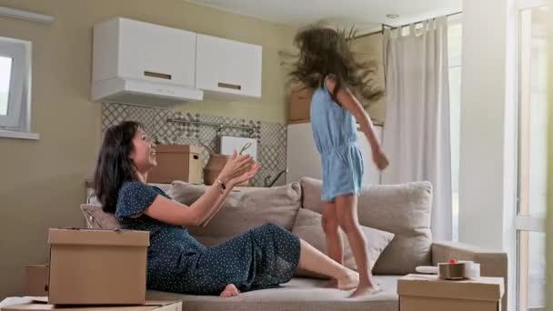 Mladá matka a její dcera skákají do postele. Vtipná polštářová bitka. Hrát společně a vychutnat si moment Rodinný čas o víkendu.