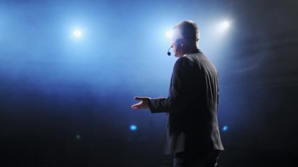 Zadní pohled na muže hovořící přes mikrofon v temném konferenčním sále. Osoba říká o marketingu a managementu pro úspěšné prodeje studentům v interiéru detailní záběr. Profesionální nápady