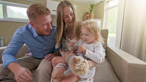 Šťastná roztomilá holčička běh objevování nového domu, zatímco rodiče objímání na pohovce, rodina s aktivní dítě dcera hrát na pohybující se den koncept