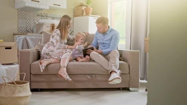 Veselá bělošská rodina s holčičkou sedící na pohovce, smějící se a sledující na tabletu něco velmi legračního. Doma. Pozitivní pohled na přemístění nebo vybalení krabičky.