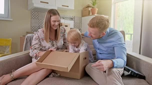 Rodiče a dvě dcery sedí na podlaze a vybalují rodinný kufr v novém domě