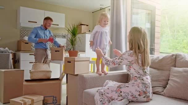 glückliche Familie beim Packen von Kartons im Zimmer. Bewegendes Konzept