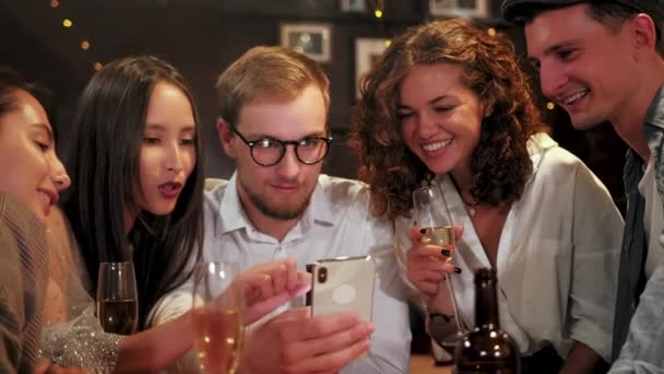 Friends, men, women, leisure, friendship and technology concept - friends with smartphones drinking beer at bar or pub