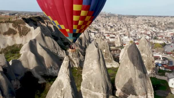 Colourful Red Blue Yellow Colours Hot Air Baloons Aerial Drone Flight. The great tourist attraction of Cappadocia. Cappadocia landscape with rocks and houses. Goreme, Cappadocia, Turkey