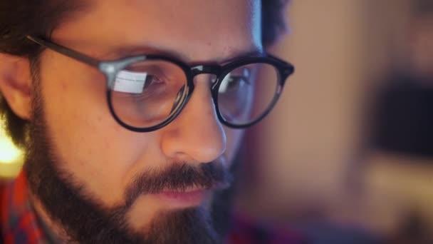 Nahaufnahme Porträt eines bärtigen jungen Geschäftsmannes mit Brille, der in seinem Büro sitzt und spät in der Nacht auf den Monitor am Computer schaut. Computerbildschirm spiegelt sich in seiner Brille.