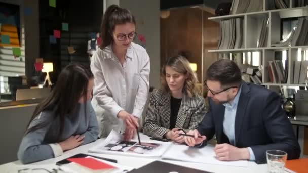 Team Of Creative Designers Are Looking At The Project Magazine, Talking About Them, Sitting Together At The Table. Modern Informal Office. Friendly Working Atmosphere