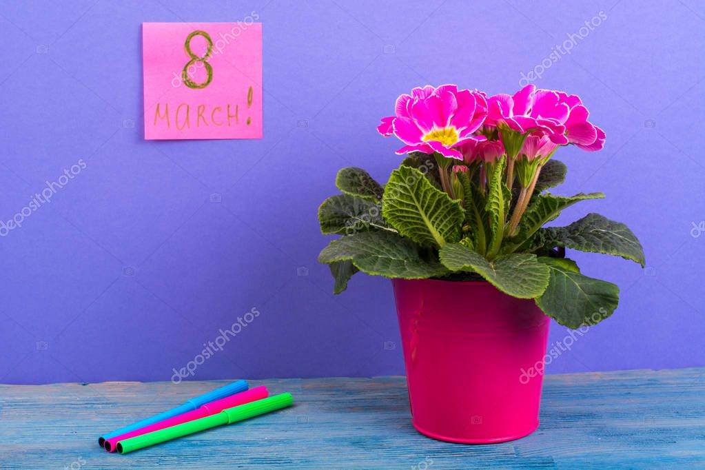 International Womens Day March 8. Reminder, sheets on bright background. Bouquet of flowers on wooden table