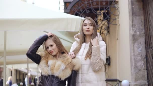 Stylish models posing to camera in fur coat in shopping center 4K
