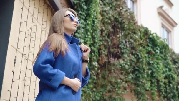 Módní dívka dívá stranou v modrém kabátě na ulici 4k