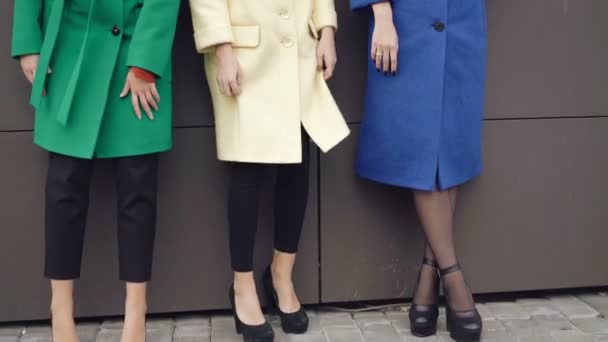 Tři stylové modely pózuje pro kamery v pláštích blízko zdi 4k