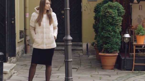 Fashionable girl posing in furry jacket on the street