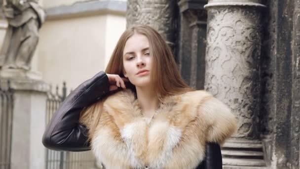 Roztomilá dívka flirtování v chlupaté sako a Pózování na ulici. Pomalu