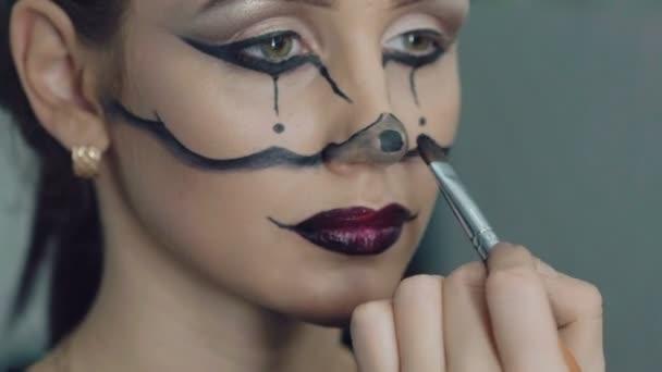 Artist drawing girl halloween makeup in art studio