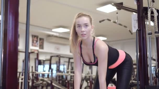 Happy sportswoman lifting dumbbells in pose in the gym 4K