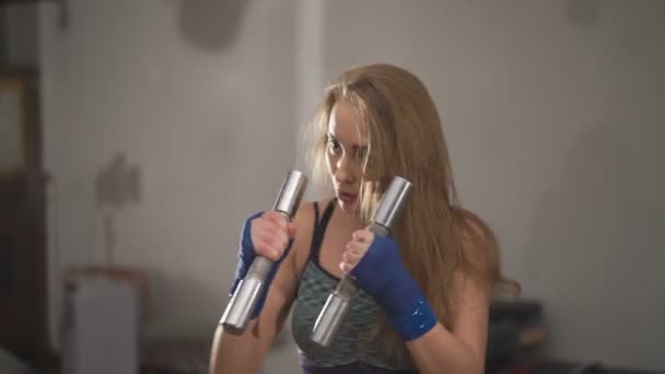 Beautifull woman punching while holding weights