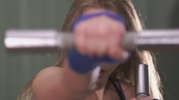 Pretty girl working out with dumbbels in front of the camera. Slowly