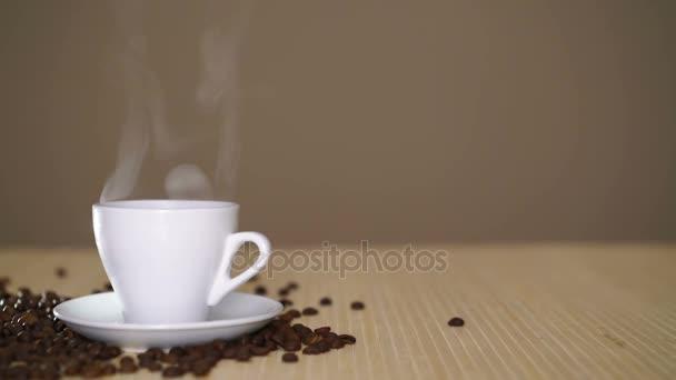 Bílý hrnek odpařovací kávu na stole s restovanými fazolkami na 4 k