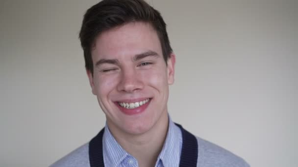 Mladý muž se vážně na fotoaparát a usmívající se v rozlišení 4k
