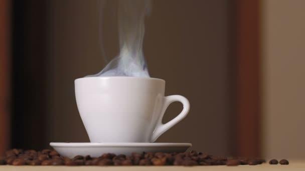 Zblízka bílý šálek odpařovací kávy na stole poblíž pražených zrn. Pomalu