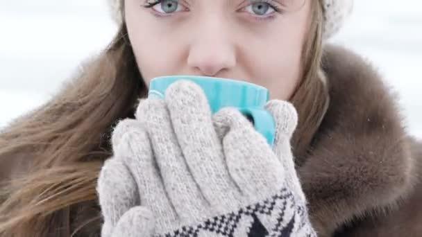 Zblízka hezká dívka pít horké nápoje venku v zimě