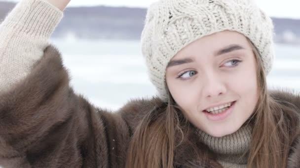 Hübsches Mädchen steht im Winter auf der Straße in Pose. langsam