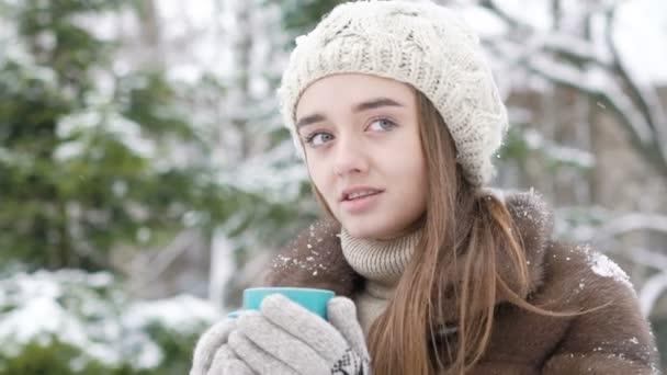 Ivott egy csésze forró ital kültéri téli napon a csinos lány