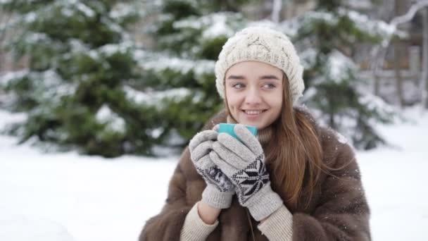 Roztomilá mladá dívka pití horké kávy venku v zimě den 4k