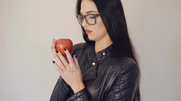 Pretty girl in glasses holding red juicy apple on the background 4K