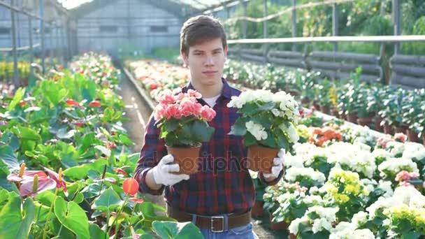 Happy gardener holding flowerpots and smiling 4K