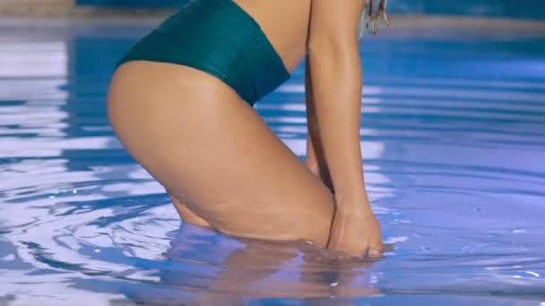 Close up of sexy wet girls buttocks posing in bikini in basin. Slowly