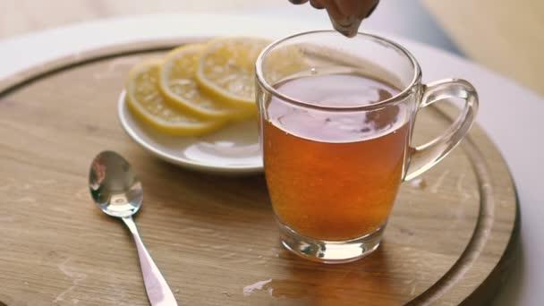 Rotující dřevěné pozadí s čajem a plátky citronu