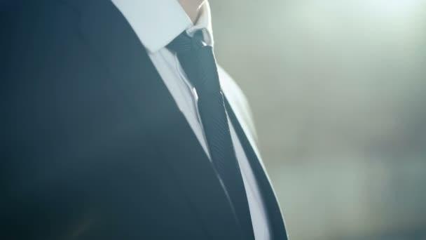 Primo piano di uomo daffari sicuro regolando la sua giacca e cravatta. 4k