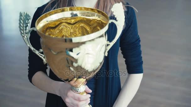 Portrét krásné dívky s zlaté zářící trophy pohár při pohledu na okna 4k