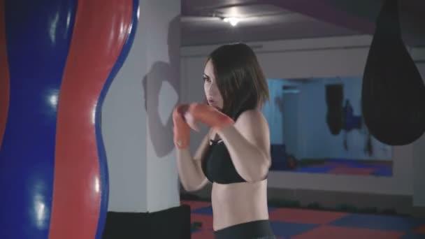 Hezká kickbox žena školení boxovací pytel ve sport studiu v rozlišení 4k