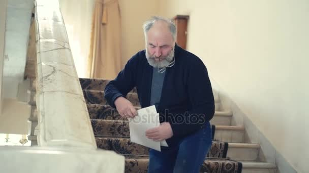Tired old producer gathering scattered papers in 4K