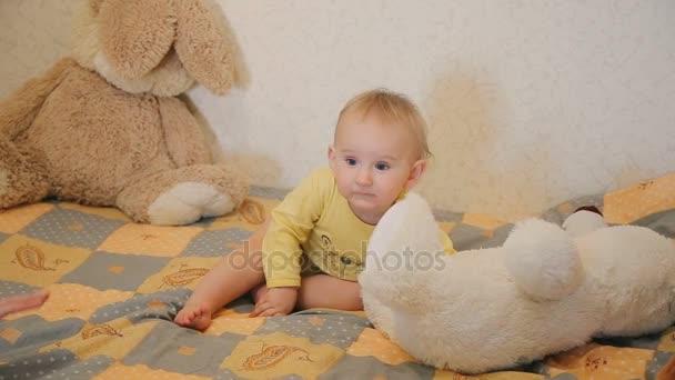 Usmívající se roztomilé dítě při pohledu na fotoaparát a hrát si s Medvídek